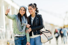 Two young women taking a self portrait of themselves Royalty Free Stock Photo