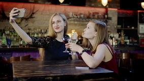 Two young women is taking selfie and clinking glasses in the bar stock footage