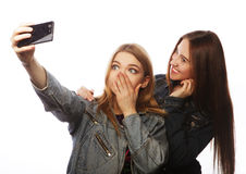 Two young women taking selfie with mobile phone Royalty Free Stock Photography