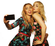 Two young women taking selfie with mobile phone. Life style, happiness, emotional and people concept: two young women taking selfie with mobile phone Royalty Free Stock Photo