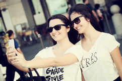 Two young women taking a selfie with the smart phone Stock Image