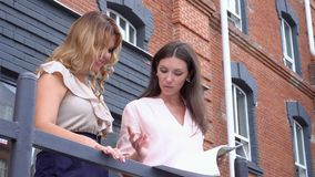 Two young women talk on a balcony of office about the transaction. Women on a sofa discuss goods samples. On this video you can see as the woman shows to the stock footage