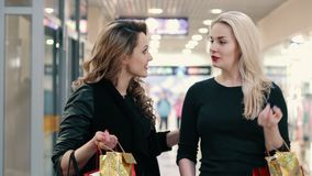 Two young women communicate during shopping at the mall. Two young women talk and walk while shopping at the mall stock video footage