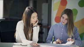 Two young women talk and write sitting at table indoors. stock video footage