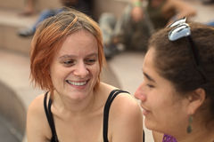 Two Young Women Talking. Young Caucasian women talking to a young Peruvian friend (Selective Focus, Focus on the eyes of the Caucasian woman Royalty Free Stock Images