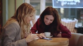 Two young women talking in a cafe and gesturing looking at photos on smartphone. Gorgeous blonde woman in beige suit is talking to her brunette friend in a dark stock footage