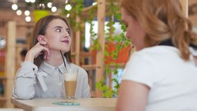 Two young women talking and drinking coffee sitting in cafe. Conversation in cafe stock video