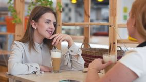 Two young women talking and drinking coffee sitting in cafe. stock video