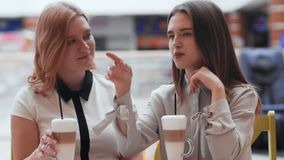 Two young women talking and drinking coffee sitting in cafe. Conversation in cafe stock video footage