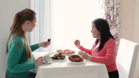 Two young women talking over coffee. Breakfast two young woman. Young woman drinking coffee and talking. A conversation. Young woman drinking coffee and talking stock video footage