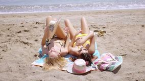 Two young women tanning in their bikinis. In the hot summer sun lying side by side on rowels on a tropical beach  head to toe view stock video footage