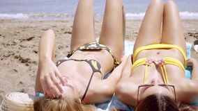 Two young women tanning in their bikinis. In the hot summer sun lying side by side on rowels on a tropical beach  head to toe view stock video