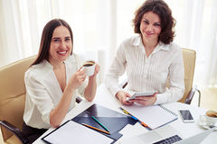 Two young women teamworking and drinking coffee in the office stock photos