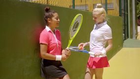 Two young women tennis players relaxing off court. Standing chatting in front of a practice wall stock video