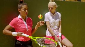 Two young women tennis players relaxing off court. Standing chatting in front of a practice wall stock footage