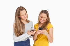 Two young women texting on their cellphones Royalty Free Stock Photos