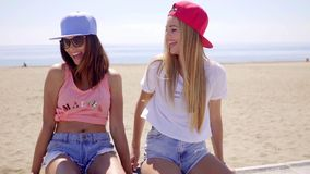 Two young women with their skateboards. Two sexy trendy young women with their skateboards relaxing sitting on a low wall overlooking a beach chatting and stock video