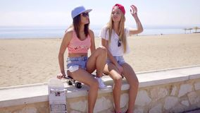Two young women with their skateboards. Two sexy trendy young women with their skateboards relaxing sitting on a low wall overlooking a beach chatting and stock footage
