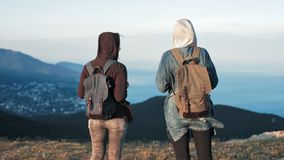 Two young women tourist with backpack walking at rock of mountains with beautiful nature landscape at background stock video