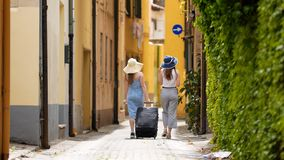 Two young women tourist traveling on the road in Dolomites with big backpack and guitar holding a map. Mid shot stock photography