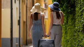 Two young women tourist traveling on the road in Dolomites with big backpack and guitar. Mid shot stock images