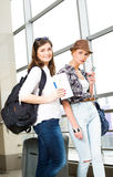 Two young women tourists holding a card and passport and looking at the camera Stock Photo