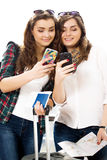 Two young women tourists holding a passport and make selfie terminal Royalty Free Stock Photography