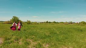 Two young women in traditional Russian clothes run across the green field. Shot form drone stock footage