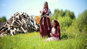 Two young women in traditional russian clothes singing songs by the balalaika on the background of firewoods. Mid shot stock video footage