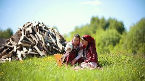 Two young women in traditional russian clothes sitting on the field and taking a selfie. Mid shot stock footage
