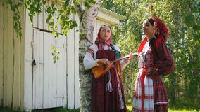 Two young women in traditional Russian clothes standing near a wooden building one of them play balalaika. Two young women in traditional Russian clothes stock footage