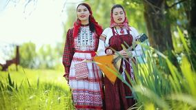 Two young women in traditional russian clothes walking on the field and singing - one of them holding balalaika. Mid shot stock video