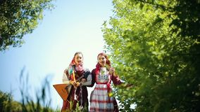 Two young women in traditional russian clothes walking on the field and singing a song and one of them holding balalaika. Mid shot stock video