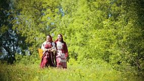 Two young women in traditional russian clothes walking on the field and singing a song - one of them holding balalaika. Mid shot stock video footage