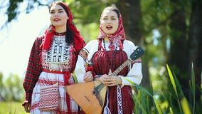 Two young women in traditional russian clothes walking on the field and singing a song. Mid shot stock video footage