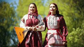 Two young women in traditional russian clothes walking in the forest and singing a song - one of them holding balalaika. Mid shot stock video