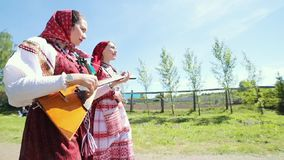 Two young women in traditional russian clothes walking on the road in the village. Mid shot stock video