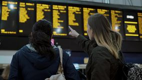 Two young women at a train station checking departure times. Travel photography stock video