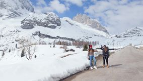 Two young women traveling in Dolomites. Catching a car on a road stock video footage