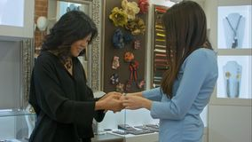 Two young women try on a desined jewellery in a store royalty free stock image