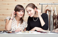 Two young women trying on earrings. On wooden background. Clothes, cosmetic and accessories around them Royalty Free Stock Photo
