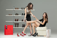 Two young women trying on high heels. Two cucasian young women trying on high heels Stock Photo