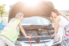 Two young women with broken car. Looking at engine bay with hood open stock photos