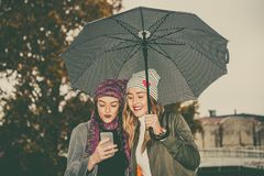 Two young women with umbrella and using mobile phone in the stre Stock Photo