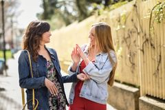 Two young women in urban background. Lifestyle concept. Two happy young women talking in urban background. Lifestyle concept royalty free stock photo