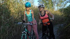 Two young women use GPS Navigation At Smartphone On Bicycle while Cycling