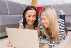 Two young women using computer while lying down on floor in living room Stock Photo