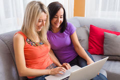 Two young women using computer while sitting on couch in living room Stock Photo