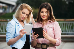 Two young women using a digital tablet computers Stock Photography