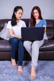 Two woman using a laptop computer on sofa in living room at home. Two young women using a laptop computer on sofa in living room at home Royalty Free Stock Images
